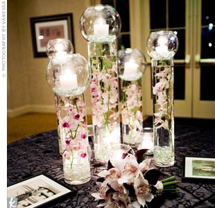 The escort card table also had large glass cylinder vases with dendrobium orchids submerged in water. Each cylinder was then topped with a glass bubble filled with a column candle.