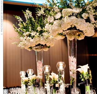 Tall trumpet vases topped with white snapdragons, larkspur, and spider mums, and filled with submerged white cymbidium orchids designated the head table.
