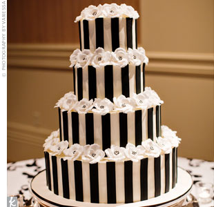 The four-tiered black-and-white striped cake was accented with handmade white sugar flowers. Inside, the cake was white with lemon-raspberry filling.