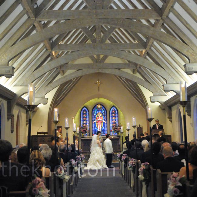 With the vibrant blue stained-glass windows and natural wood-beamed ceiling, little other decor was needed, just dainty clusters of lilies, roses, and hydrangeas hanging from the pews down the aisle.