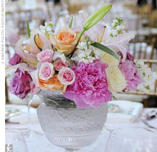 White ceramic vases filled with peonies, lilies, and roses were among the shorter centerpieces.