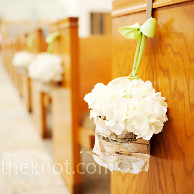 Sarah wanted a wintry forest feel, so arrangements of hydrangeas in birch tree bark-wrapped vases lined the pews of the church.