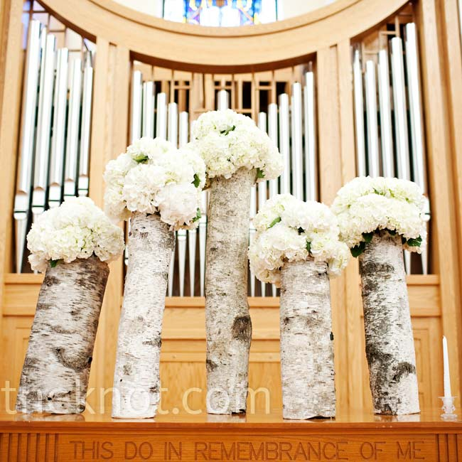 Vases wrapped in birch tree bark held white hydrangeas and added a fresh, rustic look to the church.