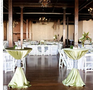 A mix of square and circular tables, topped with gray table runners and mossy green napkins, were set up throughout the space.