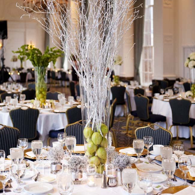 The ballroom was set with white linens, gold chargers, and varied centerpieces -- some had fresh pears and tall silver branches.
