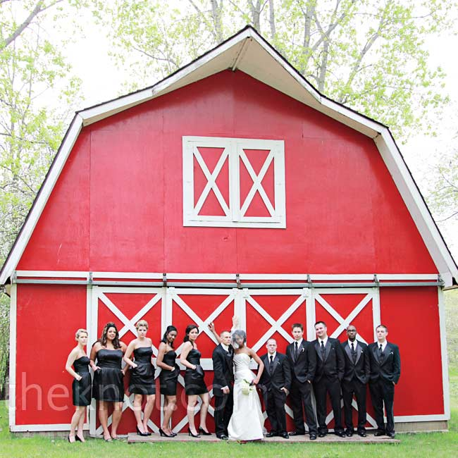 The black tuxedos and bridesmaid's dresses looked chic against the red barn.
