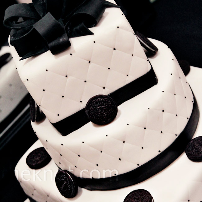 The three-tier black-and-white cake had ivory fondant on all tiers with a quilted pattern and black dots wrapped with a black fondant ribbon.
