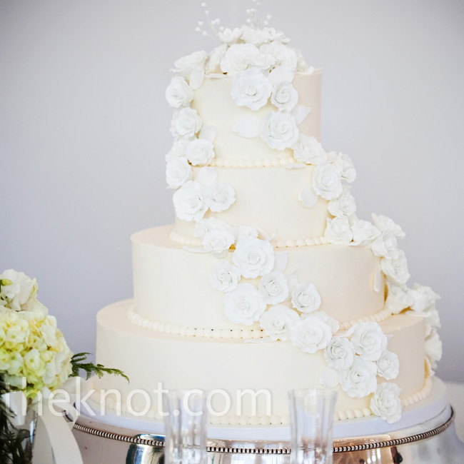 The four-tiered white cake with Italian meringue buttercream frosting had swiss dotting around each layer and a cascade of fondant roses wrapped around the entire cake.