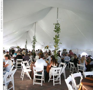 Leaves and branches covered the tent poles, giving the space an outdoor feel even under the large white tent. All tables were covered with brown linens and had red-orange napkins at each place setting.