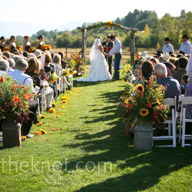 The bride walked down the aisle, which had been lined with Mason jars filled with flowers, wheat or candles, hanging off of shepherd's hooks. They exchanged vows under a rustic arch decorated with fall flowers.
