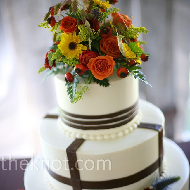 The wedding cake was a white three-tiered confection with brown stripes topped with jewel-toned flowers. In addition to drinks, there was a hot chocolate bar, complete with whipped cream, marshmallows, and sprinkles.