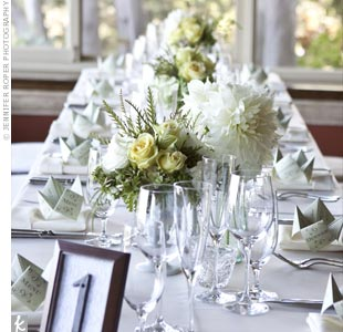 The couple opted for low arrangements of white and yellow to line the center of the long dining tables.