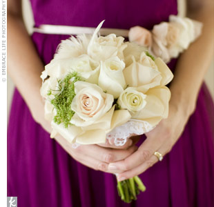 Morgan's bridesmaids carried petite bouquets of white and ivory garden roses accented with cream feathers and pearls.