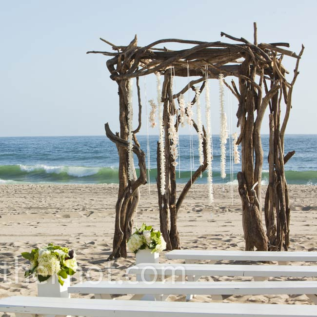 For a rustic twist on their beach setting, Morgan and Brett exchanged vows beneath a driftwood arch decorated with strands of hanging white orchids.