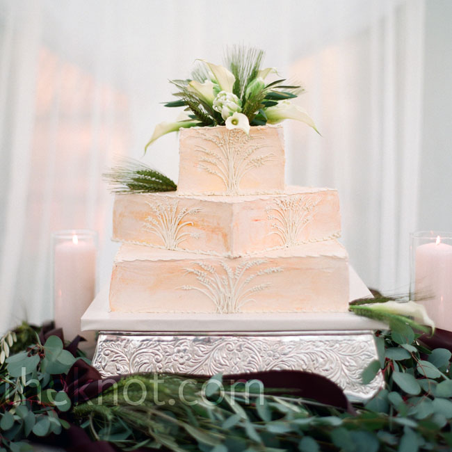 Fresh flowers and greens topped the couple's cake. All three square tiers were offset for a modern look.