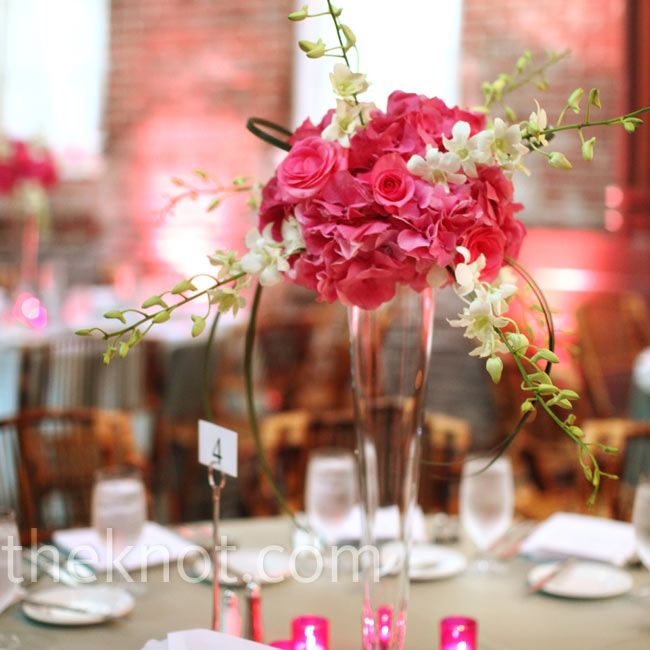 For a striking focal point, orchids branched out from round arrangements of pink roses displayed in tall glass vases. Matching pink votive holders grouped around the bottom of the vases.