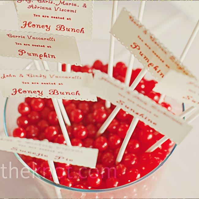 "Jars of bright red candies displayed the escort cards. ""Later, we let guests fill bags with the candy as favors,"" says the bride."
