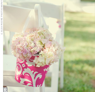 The couple used the pink damask details on the tin buckets filled with hydrangeas that marked the ceremony chairs.
