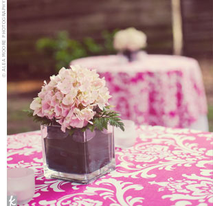 Short, square vases filled with pink hydrangeas subtly complemented the texture of the hot pink damask table overlays.