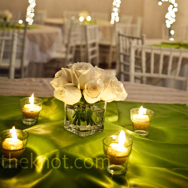 Glittery-gold candles flickered around square containers packed with ivory roses. Green squares of satin gave a shimmery pop of color to the ivory linens.