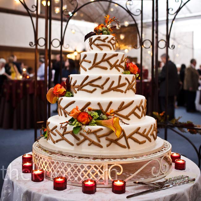 The bride and groom saved money by having a friend make a five-tiered faux cake decorated with a chocolate branch motif and fresh fall flowers.