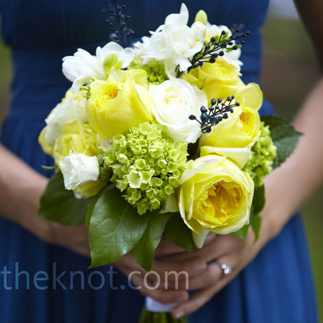 For a vibrant contrast against their vintage blue dresses, the bridesmaids carried yellow and green bouquets of hydrangeas, garden roses, and fresh blueberry sprigs.