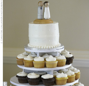 A small white cake topped with a miniature bride and groom sat atop tiers of multi-flavored cupcakes iced with buttercream.