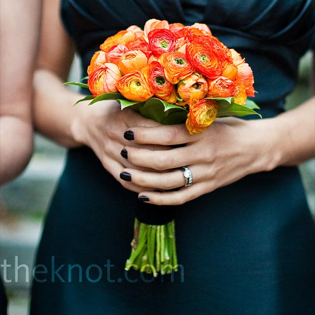 Erica's bridesmaids wore strapless black dresses and carried orange ranunculus bouquets wrapped in black.