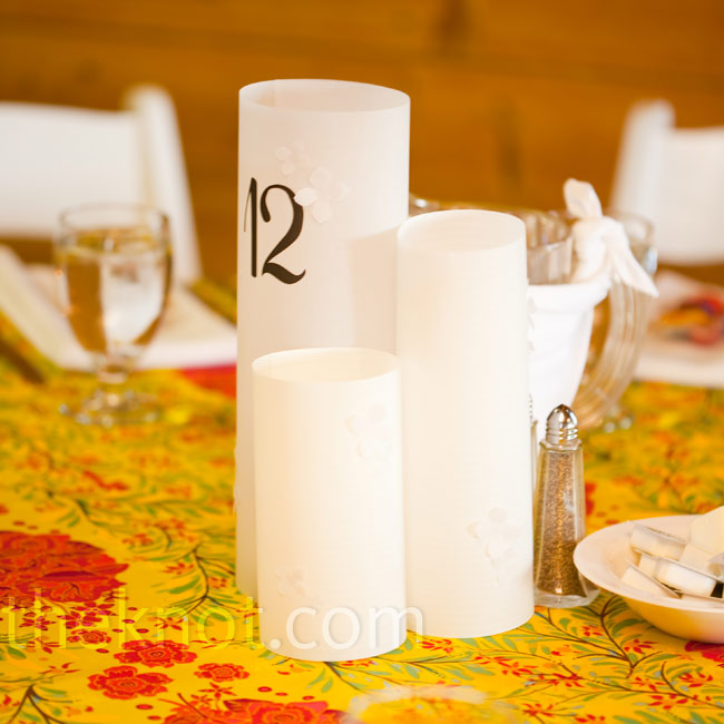 Instead of traditional vases with flowers, three simple white luminaries stood in the center of the tables.