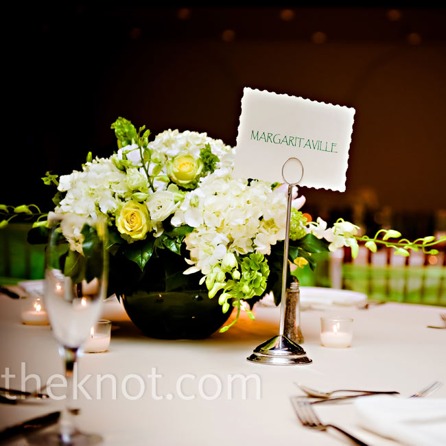 Small round vases topped the tables and were filled with white hydrangeas, green viburnum, parrot tulips, and Bells of Ireland.
