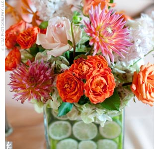 Square glass vases, filled with flowers were lined with lime or orange slices.