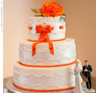 Sugar-made lace wrapped around the cakes three tiers. An orange sugar ribbon was woven through the lace of the top tier.