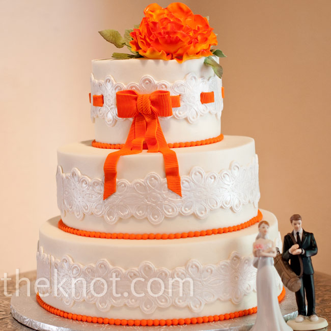 Sugar-made lace wrapped around the cake's three tiers. An orange sugar ribbon was woven through the lace of the top tier.