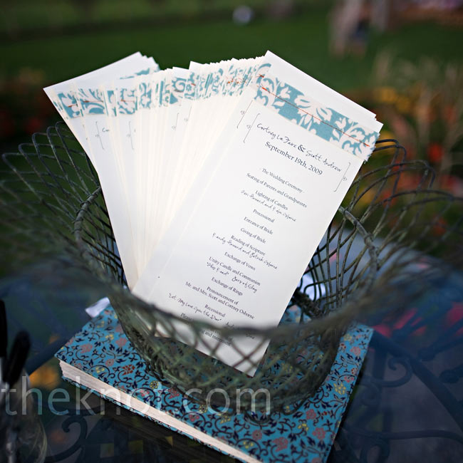 The couple designed their own ceremony programs, a strip of aqua damask fabric sewn on top with orange stitching.