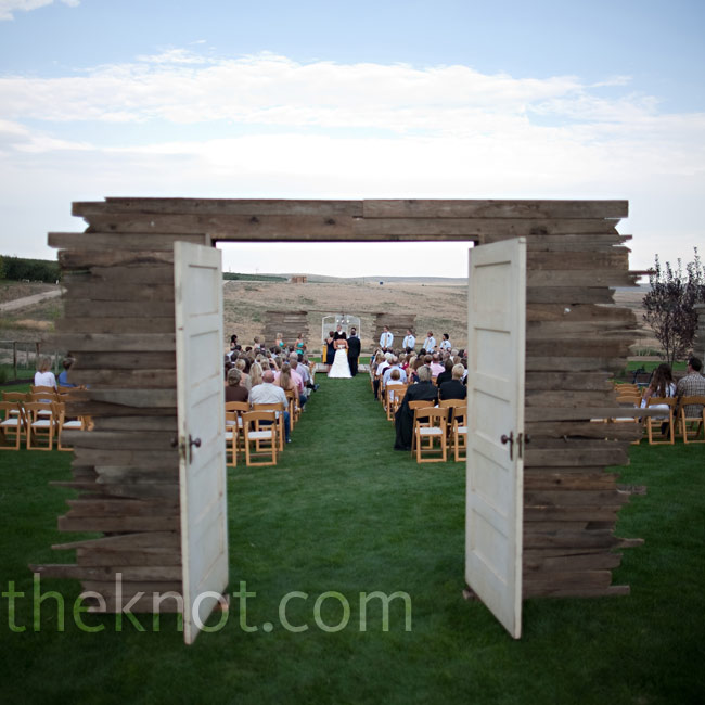 Two antique white doors flanked by barnwood half-walls defined the entryway to the ceremony.