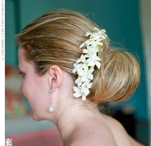 Since they were getting married on the beach and it was a little windy that day, Ashley opted to pull her hair back into a bun. Her stylist added a row of stephanotis flowers for a wedding-worthy touch.