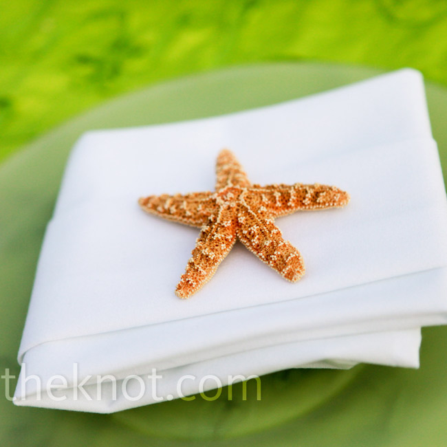 The beach chic tables were set with chargers, white folded napkins and dried starfish, which guests took home as wedding favors.