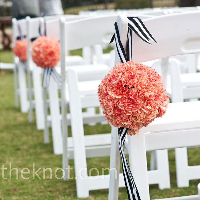Coral pomanders hung on every other aisle chair from black-and-white ribbons.