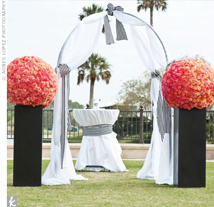 Clusters of pink carnations set on black urns by the altar, which was wrapped in white fabric tied with striped sashes.