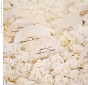 A calligrapher wrote guests' names and table numbers on round shells. The escort cards were then displayed in a bed of white flowers.