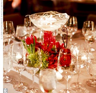 For something a little different, pedestal bowl vases topped the reception tables. The stems were filled with submerged red Mokara orchids, and votive candles floated at the top. Tulips, orchids and roses surrounded the base as well.
