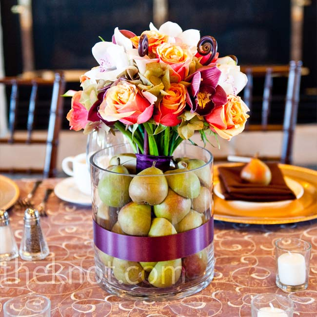 Colorful bouquets of roses, tulips, calla lilies, curly ferns and cymbidium orchids stood in the middle of vases filled with pears.