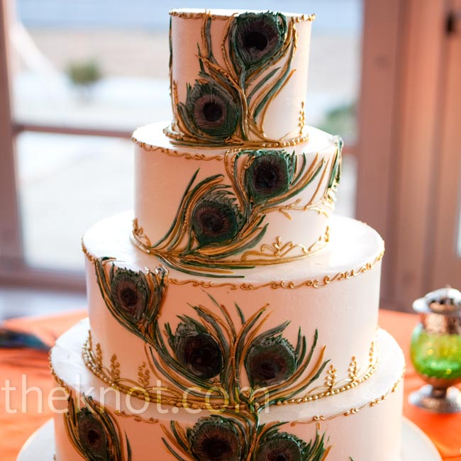 The couple's four-tiered buttercream cake was painted with gold trimming and peacock feathers.
