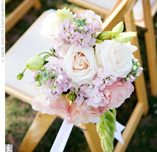 Soft bunches of roses and hydrangeas decorated chairs on the end of each row.