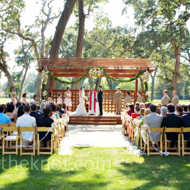Stephanie and Trey got married beneath a wooden trellis surrounded by tall oak trees. Their florist decorated with plenty of greenery and pale pink flowers.