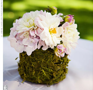 Moss-covered centerpieces that topped the tables at the cocktail hour amped up the wedding's garden look.
