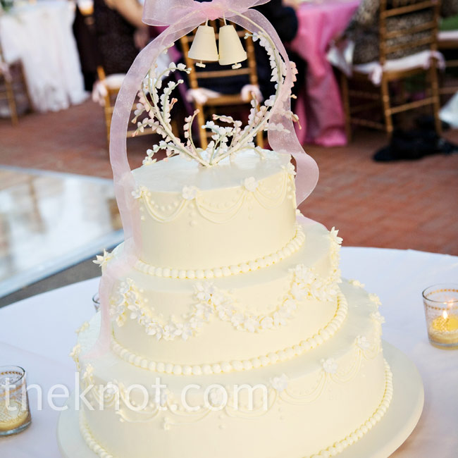 The couple served a traditional buttercream wedding cake, decorated with piping and sugar stephanotis flowers. They had their wedding bells cake topper custom made.