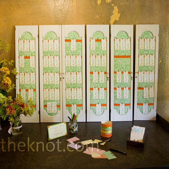 Ribbon-fastened escort cards were displayed on antique cabinet doors that had been fabric-mounted.