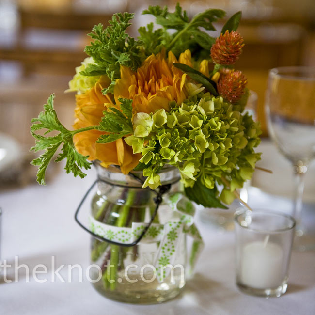 Orange and green blooms like dahlias and hydrangeas were placed in Mason jars Adrienne's mom collected.
