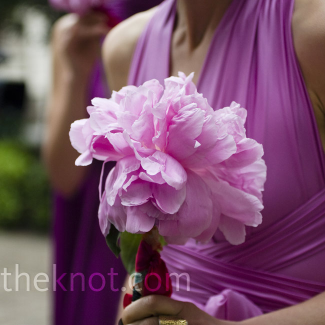 For a less stuff look, the bridesmaids wore a pink peony tied to their wrists or hair. Others carried a single stem wrapped in fabric.